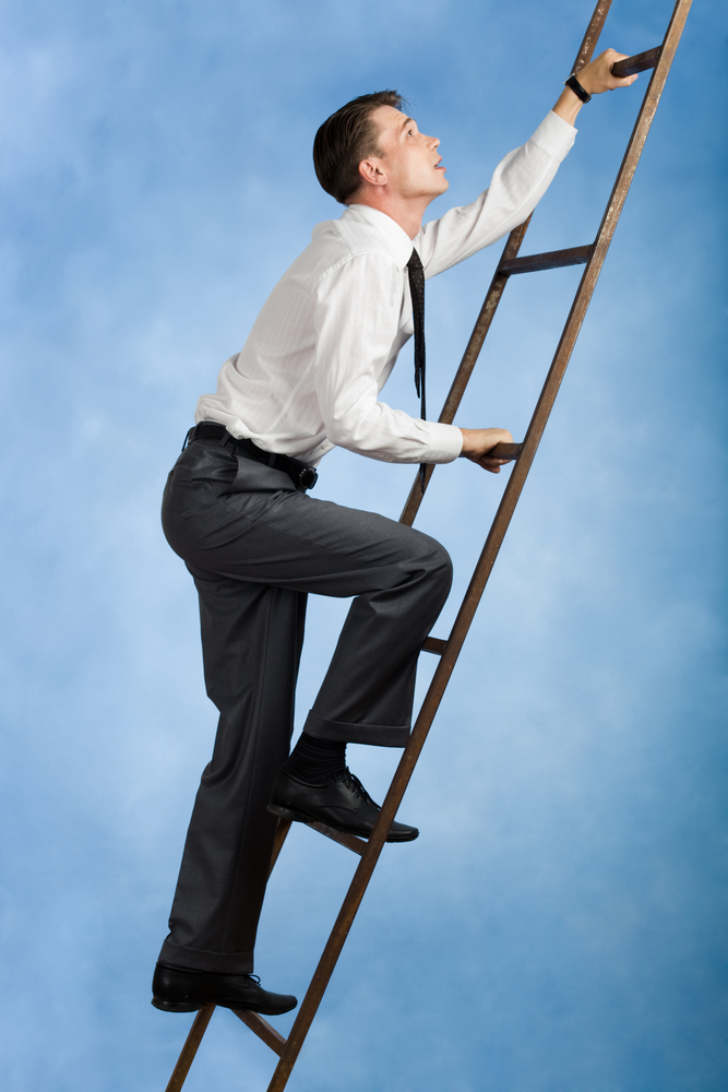Young Businessman Climbing Ladder Upwards | Shutterstock.com