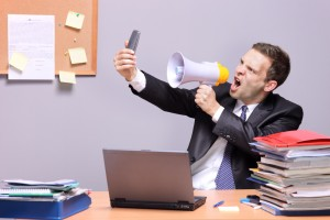 Man Yelling into Phone at Office | Shutterstock.com